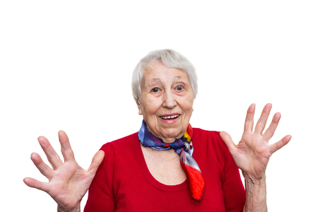 Old smiling woman with surprised expression on her face on studio background. Human emotions concept. Positive emotional old lady standing indoor