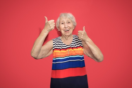 Old smiling woman with surprised expression on her face on red studio background. Human emotions concept. Positive emotional old lady standing indoor