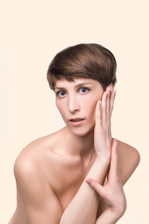 Beautiful woman. Female face close up. Portrait of young caucasian woman at studio isolated on blue. Fresh skin and beauty concept. Short haircut, long neck, perfect skin
