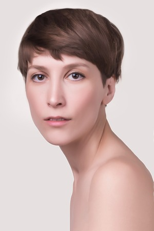 Beautiful woman. Female face close up. Portrait of young caucasian woman at studio isolated on white. Fresh skin and beauty concept. Short haircut, long neck, perfect skin