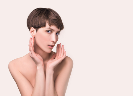 Beautiful woman. Female face and hands close up. Portrait of young caucasian woman at studio isolated on white. Fresh skin and beauty concept. Short haircut, long neck, perfect skin