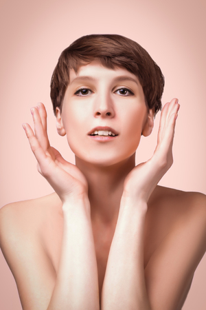 Beautiful woman. Female face close up. Portrait of young caucasian woman at studio isolated on pastel. Fresh skin and beauty concept. Short haircut, long neck, perfect skin Stock Photo