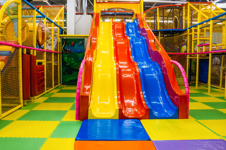 The abstract large childrens playroom with a slide and colorful balls in entertainment center, game room