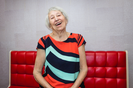 Smiling old senior 80 aged woman relaxing at home Stock Photo