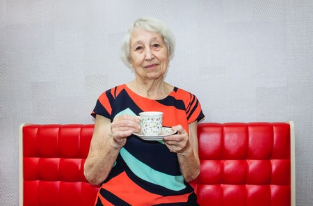 Back coffee. Happy vigorous mature woman laughing while sitting on the light background and drinking coffee