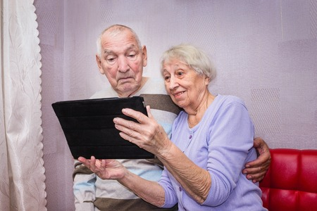 Senior surprised couple with tablet relaxing at home. Stock Photo