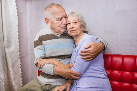 Happy senior old man and woman embracing looking at camera, romantic family couple, love care devotion in senior people marriage