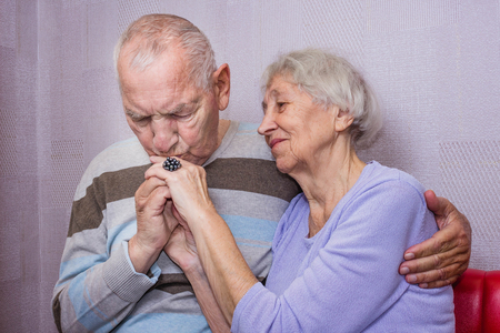 Portrait of happy senior couple, man kissing hand. of woman at home