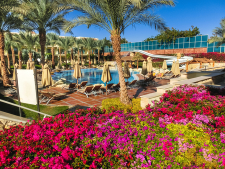 Sharm El Sheikh, Egypt - December 31, 2018: Tropical luxury Xperience Sea Breeze Resort on Red Sea beach. Swimming pool , water slide and poolside seating area with sun beds and sun umbrellas.