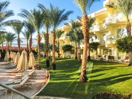 Sharm El Sheikh, Egypt - December 31, 2018:Tropical luxury Xperience Sea Breeze Resort on Red Sea beach. Palm trees and other landscaped trees on the background of a hotel buildings in Egypt, Sharm el-Sheikh Editorial