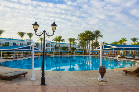 Sharm El Sheikh, Egypt - January 05, 2019: Tropical luxury Sultan Gardens Resort at Red Sea beach. Swimming pool , water slide and poolside seating area with sun beds and sun umbrellas.