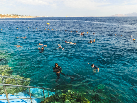 The people snorkeling in blue waters above coral reef on red sea in Sharm El Sheikh, Egypt. People and lifestyle concept Redactioneel