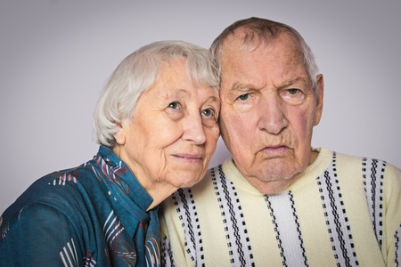 Romantic sad elderly couple sitting close together at home