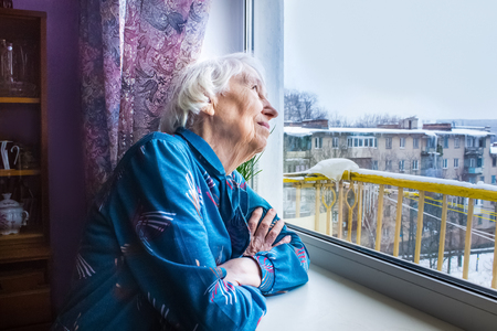 Old lonely woman sitting near the window in his house and looking and dreaming Stockfoto
