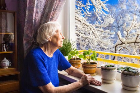 Old lonely woman sitting near the window in his house and looking at camera. Stockfoto - 118000944