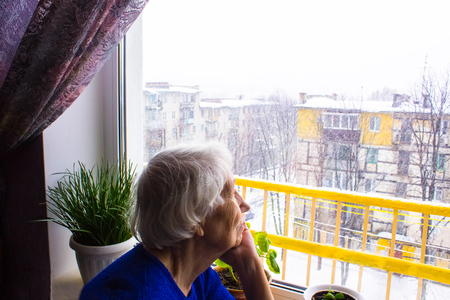 Old lonely woman sitting near the window in his house and looking at camera.