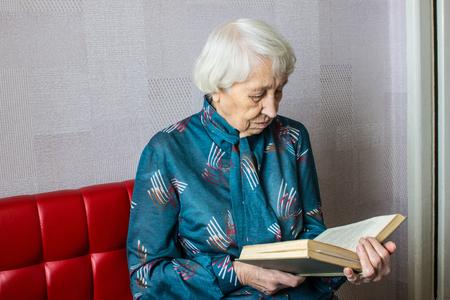 Senior woman at home reading book at home Stockfoto - 118000953