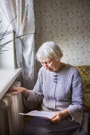 The senior woman holding gas bill in front of heating radiator. Payment for heating in winter. Stockfoto