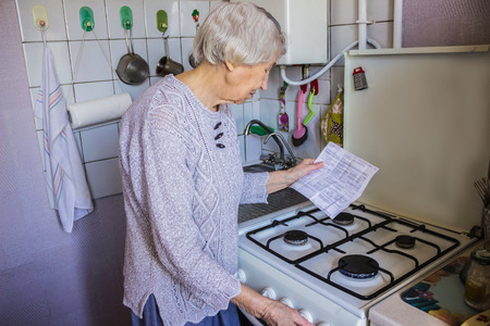 Senior old housewife at home and examines gas and electricity bills under stress when checking accounts. Stockfoto - 121271174
