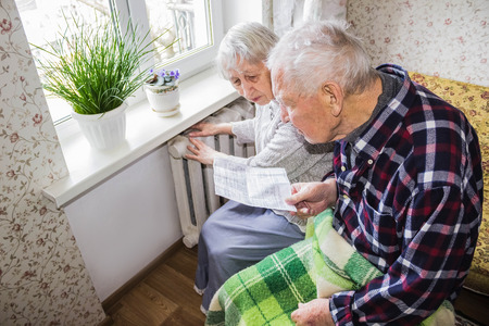 The senior woman holding gas bill in front of heating radiator. Payment for heating in winter. Stockfoto - 121271186