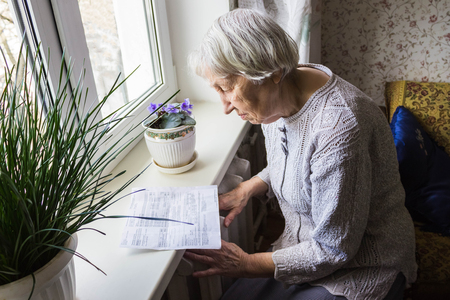 The senior woman holding gas bill in front of heating radiator. Payment for heating in winter. Stockfoto - 121271191