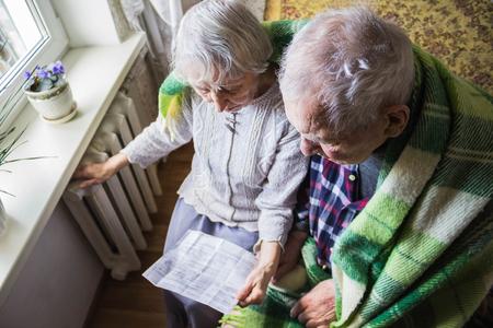 La donna anziana che tiene la bolletta del gas davanti al radiatore del riscaldamento. Pagamento per riscaldamento in inverno.