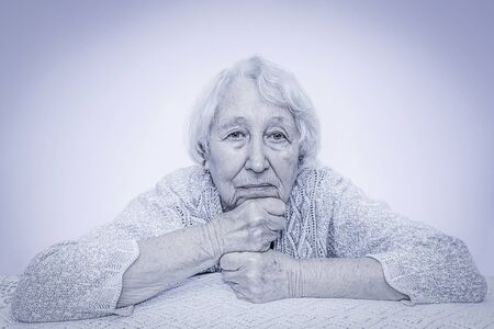 The sad senior grey haired woman dreaming on gray