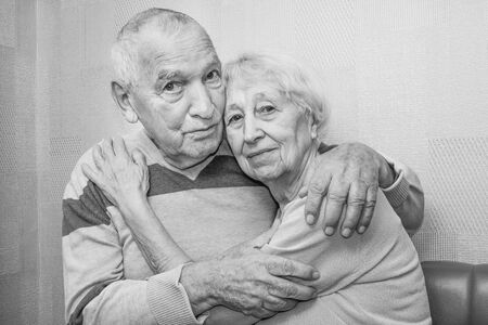 Happy affectionate mature old man and woman embracing looking at camera