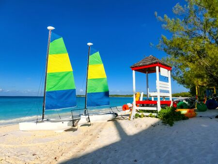 Colorful sailboats and motorboat, on a tropical beach at Half Moon Cay in the Bahamas