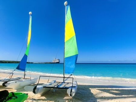 Colorful sailboats and motorboat, on a tropical beach at Half Moon Cay in the Bahamas on a tropical beach at Half Moon Cay in the Bahamas