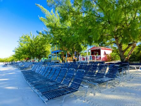 Colorful tropical cabanas or shelters on the beach of Half Moon Cay in the Bahamas with turquoise sea in the background Banco de Imagens