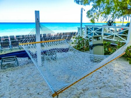 The view of hammock at beach on Half Moon Cay island at Bahamas. Blue water and white sand