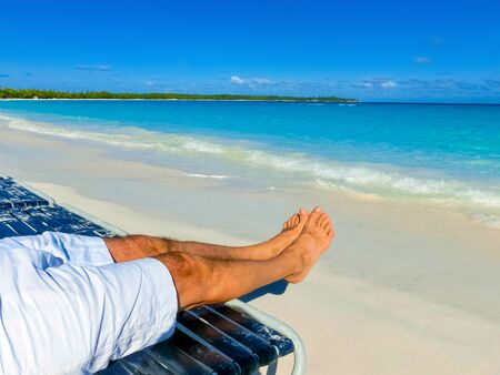 The picture of male legs over tropical beach background at Half Moon Cay in the Bahamas Banco de Imagens