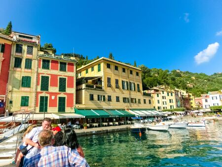 Portofino, Italy - September 13, 2019: People at boat tour at beautiful bay with colorful houses in Portofino, Liguria, at Italy