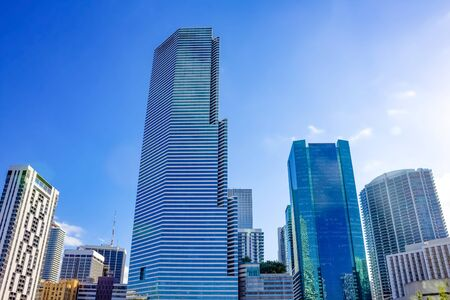 Downtown Miami cityscape view with condos and office buildings against blue sky.