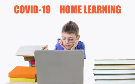 The teen boy with many books and notebook at home. Covid-19 coronavirus and home learning concept