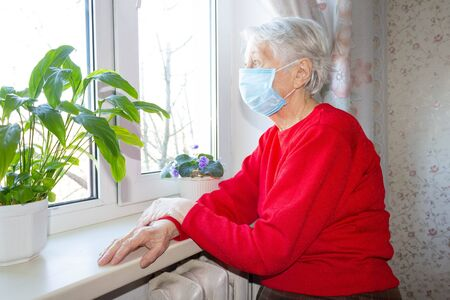 The Covid-19, health, safety and pandemic concept - senior old lonely woman wearing protective medical mask sitting near the window in his house for protection from virus