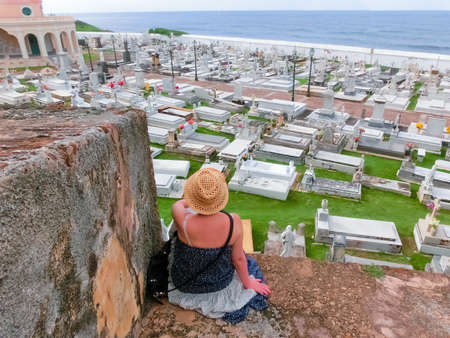 San Juan, Puerto Rico - May 08, 2016: The woman sitting near old Cemetery at San Juan at Puerto Rico and view of the ocean