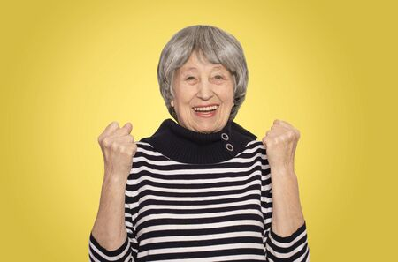 The portrait of a cheerful smiling senior woman gesturing victory over studio background Stock Photo