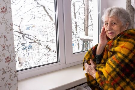 Old lonely woman sitting near the window in his house and looking at camera and smiling at winter
