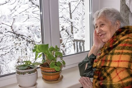 Old lonely woman sitting near the window in his house and looking and dreaming at winter