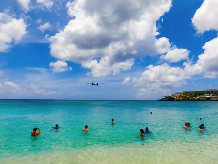 The beach at Maho Bay is one of the world's premier planespotting destinations. Airplanes landing at the Princess Juliana Airport fly over beachgoers. Фото со стока