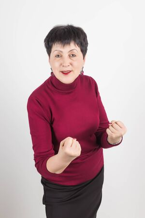 Photo of angry woman frowns face, shows fist, has dissatisfied facial expression, wears casual red clothes, threats about something, isolated over white background