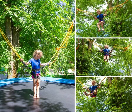 The smiling happy girl jumping with bungee in trampoline at park against green trees
