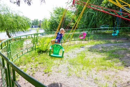 Summer concept. Girl having fun at park at carousel
