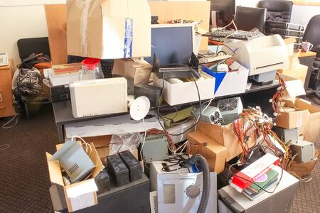 A messy desktop with stacks of files and other documents, all kind of office supplies and part of a keyboard and pc.