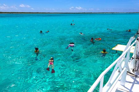 Group of friends snorkeling together on a party boat tour of the Carribean Sea at Cozumel, Mexico