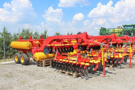 Large disc plough or harrow, towing for tractors to plow fields, against the sky