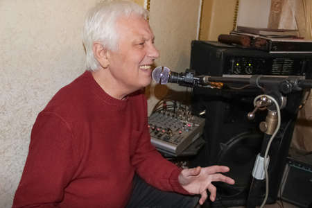 The senior old man singing in his home studio. The music, , musician, professional, song concept Stok Fotoğraf