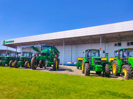 Kyiv, Ukraine - August 24, 2020: The Powerful tractors at John Deer store at Kyiv, Ukraine on June 16, 2020. Row of brand new John Deere tractors outside the store of local consortium, exhibition of latest agricultural machinery.